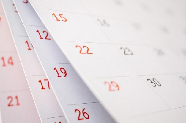 Odwracanie arkusza strony kalendarza z bliska na tle tabeli biura planowania biznesowego termin spotkania koncepcja