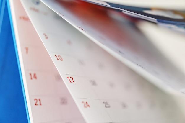 Odwracanie arkusza strony kalendarza z bliska na tle tabeli biurowej planowania biznesowego termin spotkania koncepcja