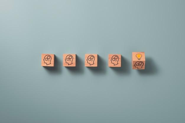 Odwracany drewniany blok kostki, na którym nadrukowana jest twarz ekranu ze znakiem zapytania do żarówki, pomysł kreatywny i koncepcja innowacji.