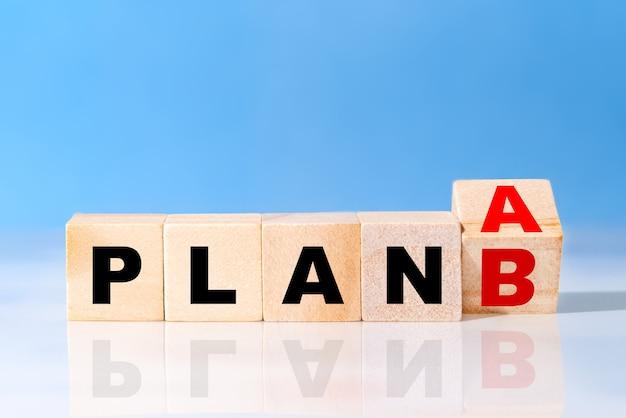 Odwróć drewnianą kostkę z napisem plan a do plan b na niebieskim tle. pomysł na biznes
