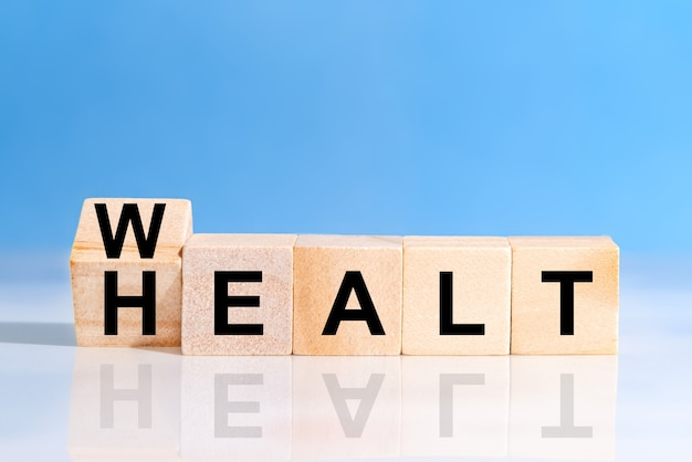 Odwróć drewnianą kostkę ze słowem bogactwo do zdrowia. inwestycja w ubezpieczenie na życie i pojęcie opieki zdrowotnej