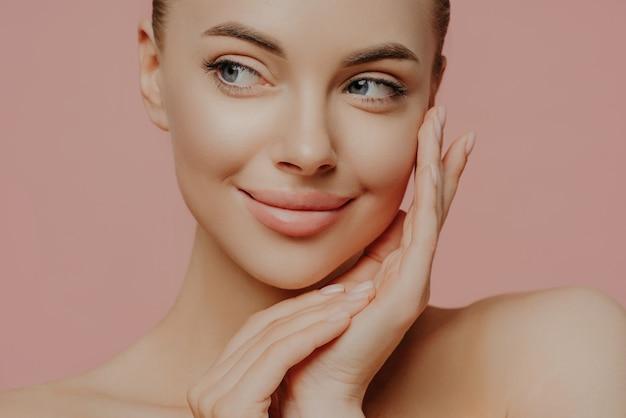Odwróć wzrok piękna młoda kobieta z czystą, świeżą skórą.