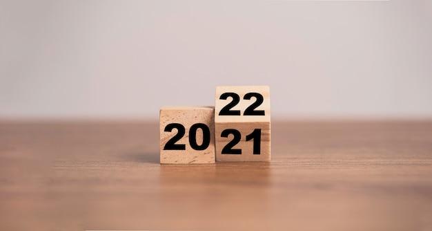 Odwrócenie drewnianego bloku kostki zmieni rok 2021 na 2022. wesołych świąt i szczęśliwego nowego roku koncepcja.