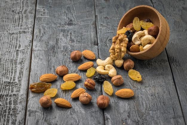 Odwrócona drewniana miska z suszonymi owocami i orzechami na drewnianym stole. naturalne zdrowe jedzenie wegetariańskie.