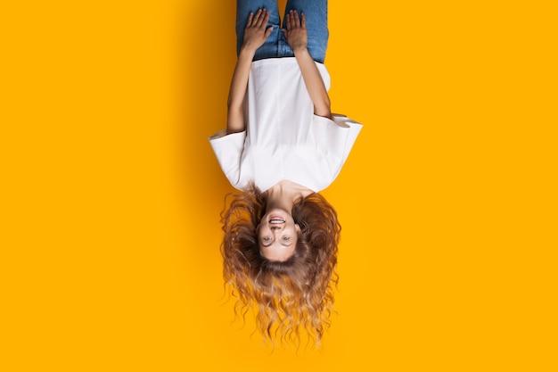 Odwrócone zdjęcie blondynki w dżinsach i białej koszulce uśmiechającej się do kamery i reklamującej coś
