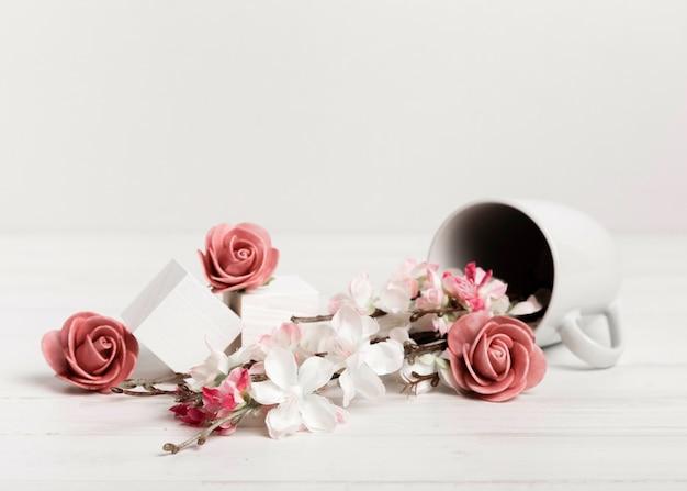 Odwrócony kubek z różami i białymi kostkami
