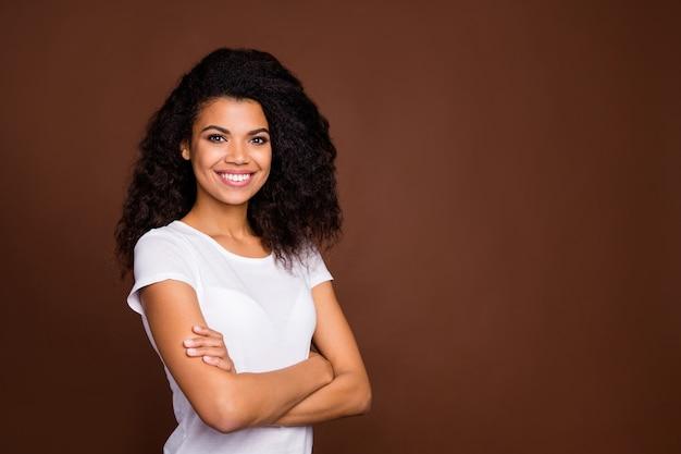 Odwrócony portret pozytywnej treści afroamerykańskiej dziewczyny poczuć przyjazne emocje skrzyżowane ręce cieszyć się weekendami nosić strój w stylu casual.