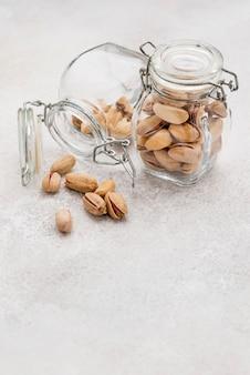 Odwrócony słoik wypełniony pistacjami na marmurowym stole do kopiowania