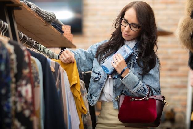 Odzież damska sklep klienta przechodzi przez odzież na stojaku w centrum handlowym.