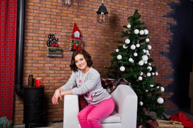 Odzież dziewczęca na zimowe swetry w pokoju z dekoracjami chrismas.