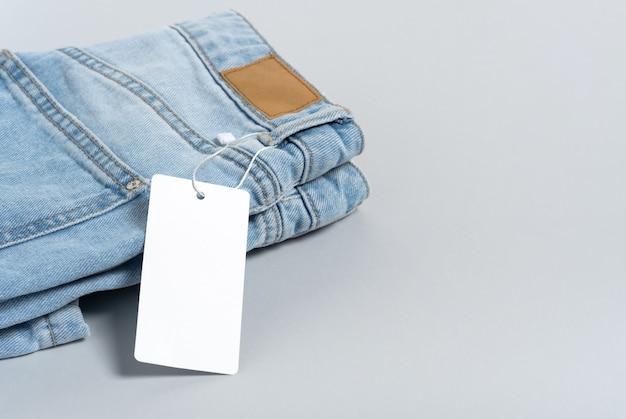 Odzież dżinsy biały znacznik papieru, etykieta pusty szablon makieta. szare tło, kopia przestrzeń, płaskie lay