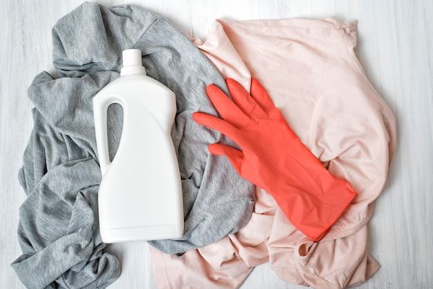 Odzież, gumowa rękawica i butelka z detergentem. widok z góry