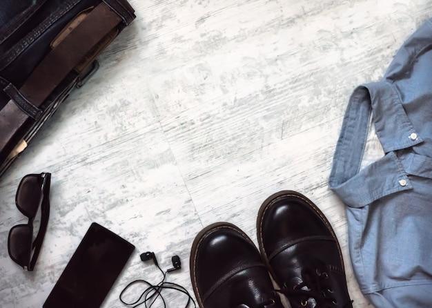 Odzież i akcesoria męskie. dżinsy, buty, okulary, smartfon na drewniane tła. widok z góry z miejscem na kopię