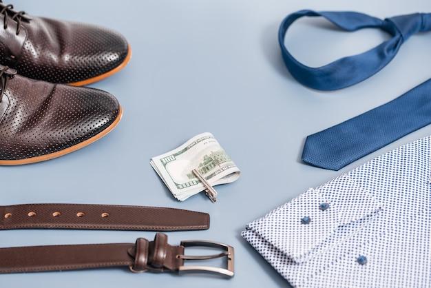 Odzież i akcesoria męskie. koszula krawat i buty, pasek pieniędzy. na niebieskim tle, skopiuj miejsce.widok z góry.
