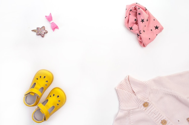 Odzież i buty dziecięce są rozłożone na białym tle w widoku z góry. miejsce na tekst.