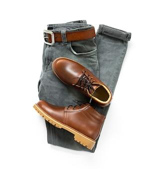 Odzież męska z brązowymi butami, paskiem i szarymi dżinsami na białym tle. widok z góry