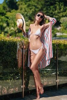 Odzież plażowa. szczupła dziewczyna z kapeluszem w dłoni i białym bikini pozuje do aparatu i uśmiecha się