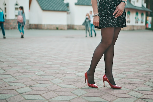 Odzież reklamowa, dziewczyna w czarnej spódnicy i czerwone buty na ulicy. manekin.
