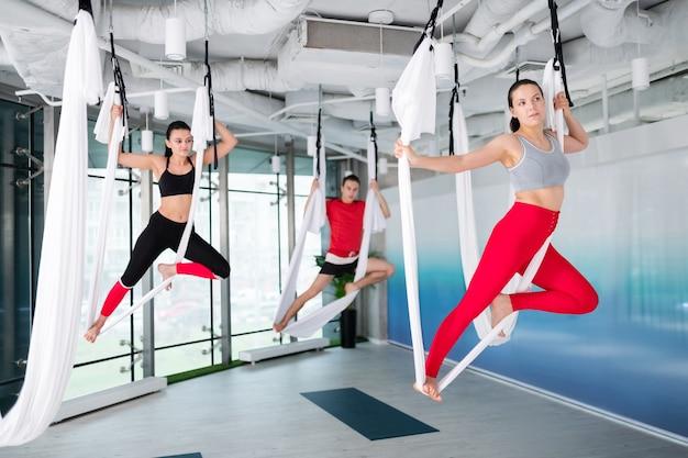Odzież sportowa. dwie kobiety i mężczyzna w wygodnych sportowych ubraniach ćwiczą razem latającą jogę po pracy