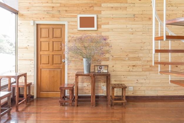 Odzyskana drewniana ściana z drewnianymi drzwiami, stołami i kwiatami w cynkowym wazonie w jasnym świetle słonecznym. przytulna i ciepła atmosfera wnętrza.