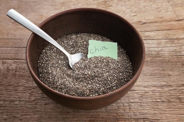 Odżywczy chia ziarna w pucharze na drewnianym tle.