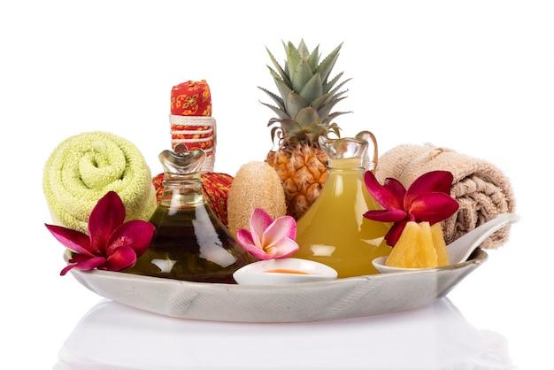 Odżywia włosy i skórę sokiem ananasowym, olejem i jajkiem żółtka na białym tle.