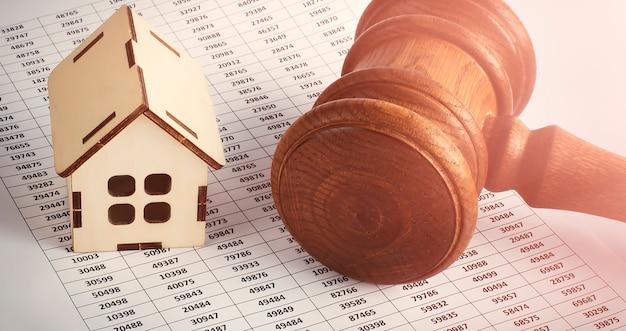 Oferowana nieruchomość. drewniany dom i młotek na tle wykresu