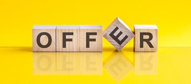 Oferta słowo napisane na bloku drewna. oferta słowna wykonana jest z drewnianych klocków leżących na żółtym stole. pomysł na biznes
