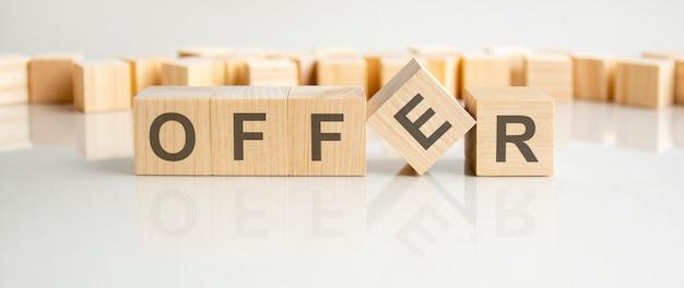 Oferta - słowo z drewnianych klocków z literami na szarym tle. odbicie napisu na lustrzanej powierzchni stołu. selektywne skupienie.