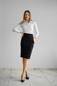 Office dress code - ładna dziewczyna w białej koszuli i obcisłej czarnej spódnicy
