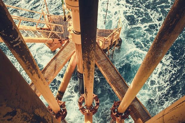Offshore wiertniczy żółty rurociąg naftowy do produkcji ropy naftowej i gazu fala morska.