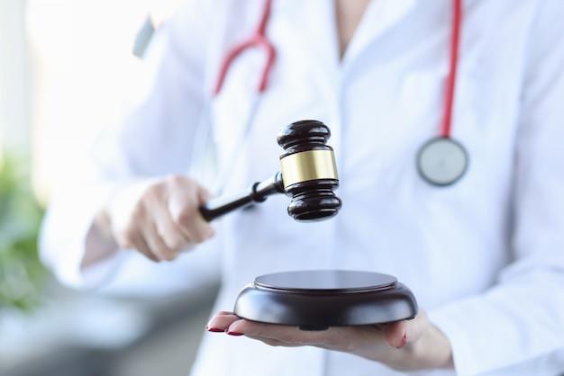 Oficer medyczny w białym fartuchu trzyma drewniany młotek dla sędziego. pojęcie medyczne spory