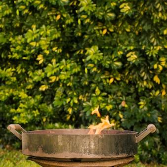 Ogień w metalowej misce grillowej na zielonym podwórku
