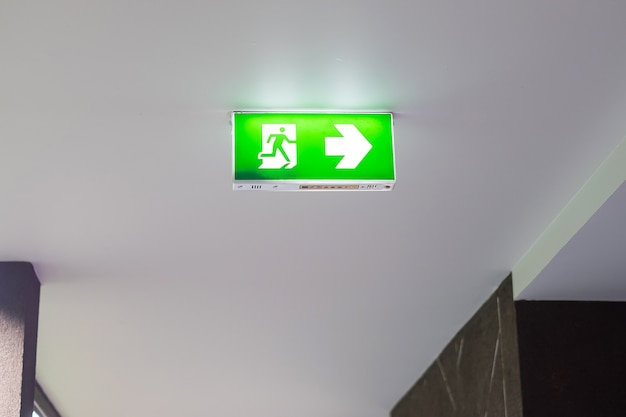 Ogień znak ewakuacyjny na tle ściany wewnątrz budynku. koncepcja bezpieczeństwa