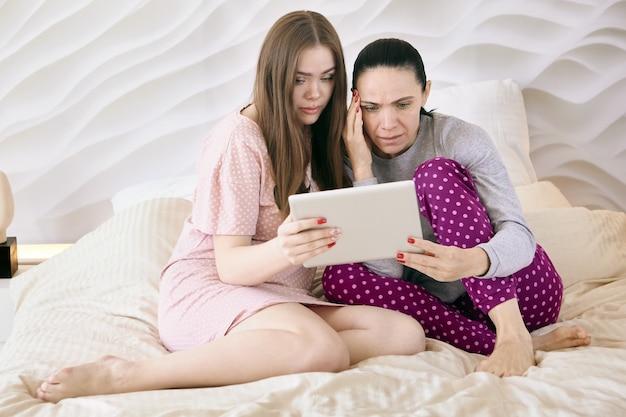 Oglądając film na ekranie urządzenia mobilnego, matka i córka ubrane w piżamy siedzą na łóżku w sypialni