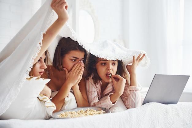 Oglądam straszny film. szczęśliwe koleżanki dobrze się bawią na imprezie piżamy w sypialni.