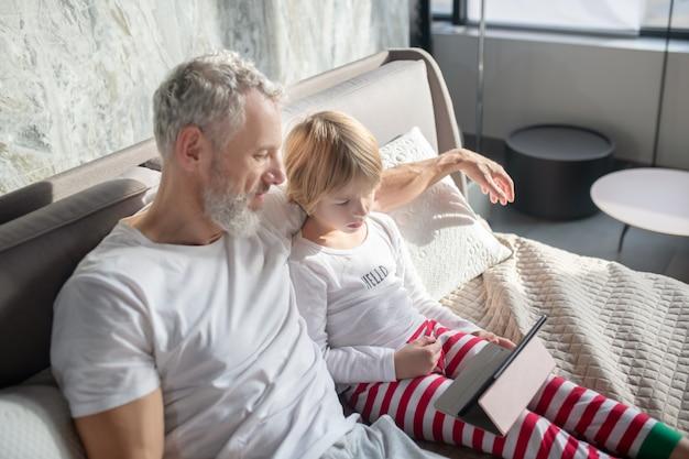 Oglądanie, ciekawe. uważny brodaty mężczyzna i dziecko w piżamie przyglądają się uważnie tabletowi w pokoju na łóżku