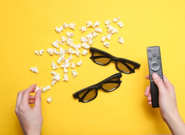 Oglądanie filmów. płaskie ręce w stylu leżącego trzymając pilota do telewizora, popcorn, dwie pary okularów 3d na żółtym. widok z góry.