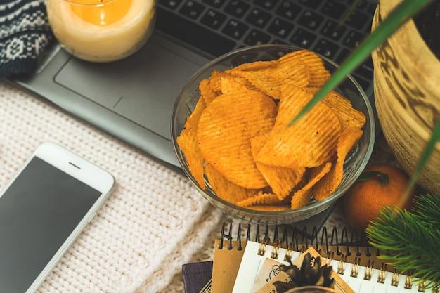 Oglądanie filmu sam w domu, niezdrowe jedzenie, przekąska, chipsy ziemniaczane w misce, laptop, przytulne zimowe tło. zdjęcie wysokiej jakości