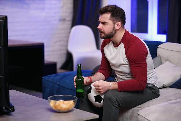 Oglądanie gry. rozochoceni młodzi człowiecy pije piwo i je przekąski podczas gdy oglądający tv