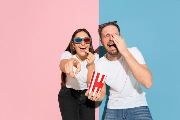 Oglądanie kina 3d z popcornem. młody i szczęśliwy mężczyzna i kobieta w ubraniu na różowej, niebieskiej ścianie dwukolorowe. pojęcie ludzkich emocji, mimiki, relacji, reklamy. piękna para.