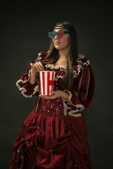 Oglądanie kina. portret średniowiecznej młodej kobiety w czerwonej odzieży vintage stojącej na ciemnym tle. modelka jako księżna, osoba królewska. pojęcie porównania epok, nowoczesności, mody, piękna.