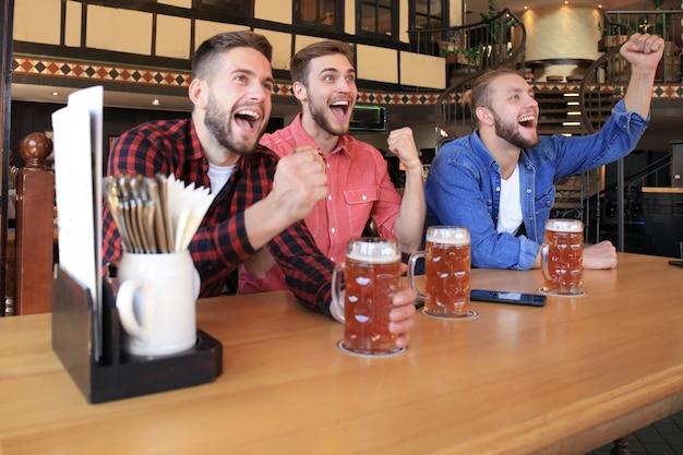 Oglądanie piłki nożnej w barze. szczęśliwi przyjaciele piją piwo i kibicują ulubionej drużynie, świętując zwycięstwo.