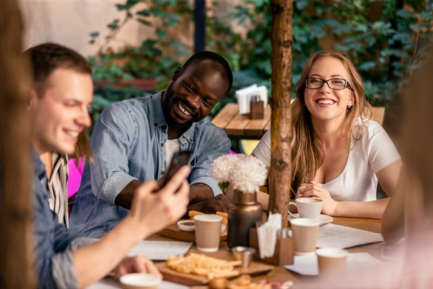 Oglądanie śmiesznego wideo w internecie ze współpracownikami w kawiarni na tarasie przy smacznym jedzeniu