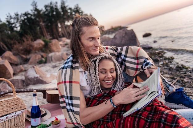 Oglądanie zachodu słońca. kochający rozpromieniony uśmiechnięta para czytanie książki podczas oglądania zachodu słońca na plaży razem