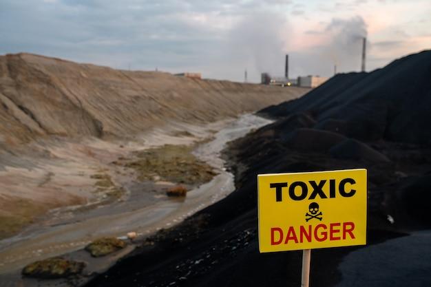 Ogłoszenie na prostokątnej żółtej tablicy informujące o toksycznym i niebezpiecznym terenie przed brudną rzeką, wzgórzami i współczesnymi fabrykami przemysłowymi