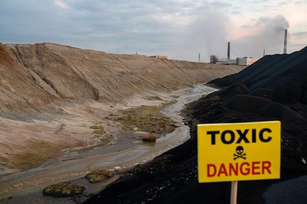 Ogłoszenie na prostokątnej żółtej tablicy informujące o toksycznym i niebezpiecznym terenie z brudną rzeką, wzgórzami i współczesnymi fabrykami przemysłowymi
