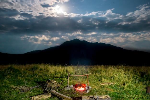 Ognisko na zielonym trawniku w pobliżu góry w nocy z ciemnym niebem i światłem księżyca