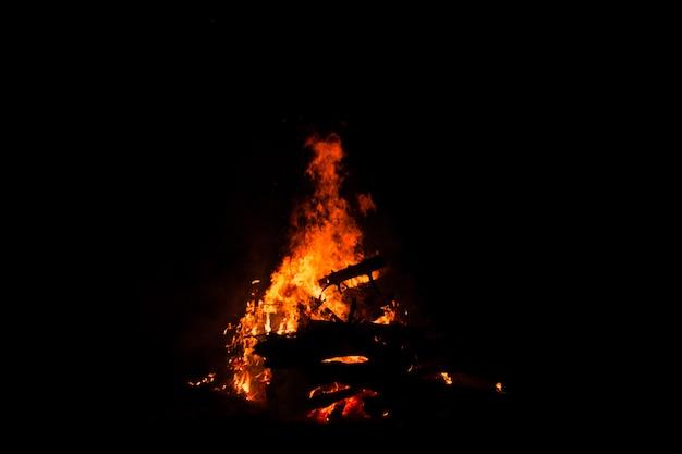 Ognisko palenie drzew w nocy. ognisko płonące jasno, upał, światło, biwak, wielkie ognisko.