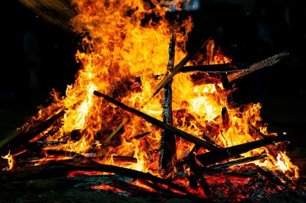 Ognisko płonące na ciemnym tle, płomień płonący drewnem.